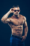 Strong athletic man  in sunglasses on black Stock Images