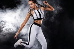 A strong athletic woman on black background wearing in white sportswear, fitness and sport motivation. Sport concept Royalty Free Stock Image