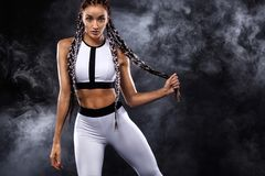 A strong athletic woman on black background wearing in white sportswear, fitness and sport motivation. Sport concept. A Strong athletic, female runner on the royalty free stock images