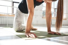 Strong athletic woman doing stretching workout on yoga mat in sunny white gym stock photography