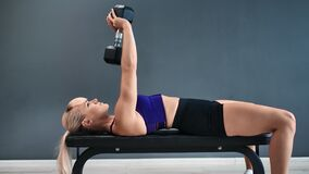 Strong athletic woman lying on sports bench during triceps muscle training. 4k Dragon RED camera