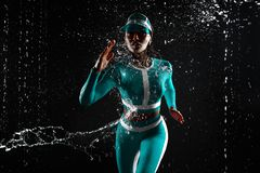 A strong athletic, woman sprinter, running on black background wearing in the mint color sportswea. A strong athletic, woman sprinter, running on black stock image