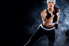 Strong athletic woman sprinter, running on black background wearing in the sportswear. Fitness and sport motivation. A Strong athletic, female runner on the stock photo