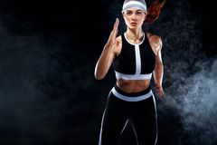 Strong athletic woman sprinter, running on black background wearing in the sportswear. Fitness and sport motivation. A Strong athletic, female runner on the stock photography