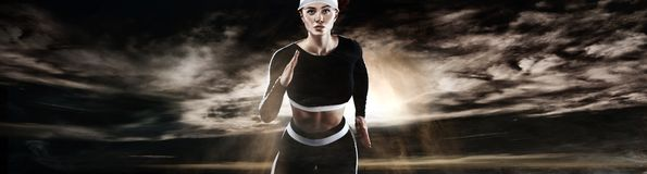 Strong athletic woman sprinter, running on dark background wearing in sportswear. Fitness and sport motivation. Runner. A Strong athletic, female runner on the stock image