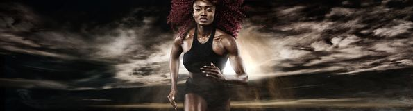 Strong athletic woman sprinter, running on dark background wearing in sportswear. Fitness and sport motivation. Runner. A Strong athletic, female runner on the stock photo