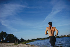 Strong attractive runner. Is during morning jog near the water Stock Image