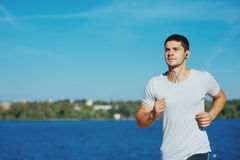 Strong attractive runner. Is during morning jog near the water Stock Images