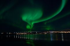 Strong aurora borealis over bridge and fjord and tromsoe city island Royalty Free Stock Images