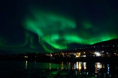 Strong aurora borealis over hill and houses Stock Photos