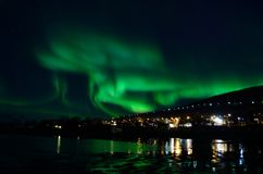 Strong aurora borealis over hill and houses Royalty Free Stock Photography