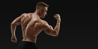Strong back of a athletic muscular man flexing his arms