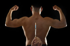 Strong back of young body building sportsman using steroids for increasing sport athletic performance. And hand holding syringe in sport cheat doping and Stock Images