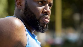 Strong bearded Afro-American sportsman seriously looking forward, close-up stock image