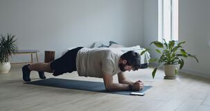 Strong bearded guy doing plank exercise, using stopwatch