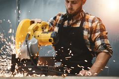 Strong bearded mechanic working on angular grinding machine in metalworking. Work in service station. Sparks fly apart. Flare effect royalty free stock photos