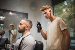 Young barber with a hair spray working on a blurred background. Stylish client in barber shop Barber occupation concept. A strong, bearded men sitting in a Stock Photos