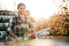 Strong bearded woodcutter wearing plaid shirt hold chainsaw in hand on background of sawmill. And warehouse of trees stock photos