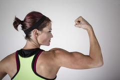 Strong Beautiful fitness woman flexing her arm and back muscles. Beautiful strong muscular woman flexing her biceps and arm muscles. View from behind to show her stock photography