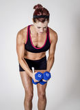 Strong Beautiful fitness woman lifting dumbbell weights Royalty Free Stock Photos