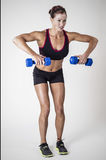 Strong Beautiful fitness woman lifting dumbbell weights Royalty Free Stock Image