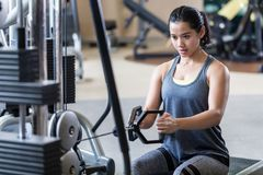 Strong and beautiful woman rowing at the cable machine during workout. Portrait of a strong and beautiful young woman sitting while rowing at the cable machine royalty free stock photos