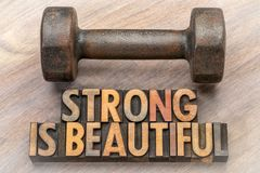 Strong is beautiful - word abstract in vintage wood type. Strong is beautiful - word abstract in vintage letterpress wood type with a vintage dumbbell stock photo