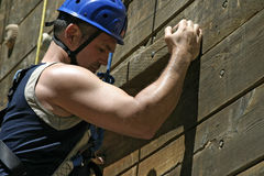 Strong Biceps Pumped Up. A climber in a helmet is reaching for the next hold up on a climbing wall. His strong biceps are showing the strain from the effort as Royalty Free Stock Photos