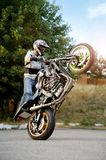 Strong biker showing extreme stunt on one wheel. Ivano-Frankivsk, Ukraine - 28 August 2015 : Stunt performer showing off extreme tricks on sport motorbike stock images