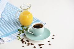 Strong black coffee in a light blue cup on a white table with orange juice. Strong black coffee in a light blue cup on a white table with orange juice Stock Photos
