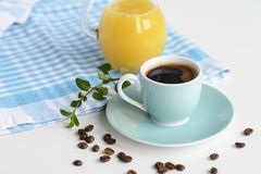 Strong black coffee in a light blue cup on a white table with orange juice. Strong black coffee in a light blue cup on a white table with orange juice Stock Images