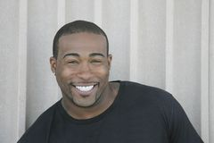 Strong black guy headshot. Closeup headshot portrait of one strong looking African American man smiling outdoors stock photo