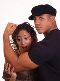 Strong Black Man showing biceps to woman. Young woman looking at large biceps on black man Royalty Free Stock Photography