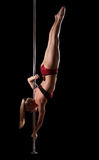 Strong blond woman posing on pole Royalty Free Stock Images