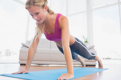 Strong blonde in plank position on exercise mat Stock Photography