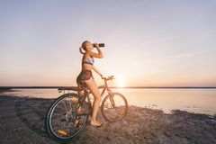 A strong blonde woman in a colorful suit sits on the bicycle, drinks water from a black bottle in a desert area near the water. Fi Royalty Free Stock Photo