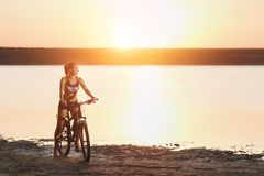 A strong blonde woman in a colorful suit sits on the bicycle near the water at sunset on a warm summer day. Fitness concept. Sky b Stock Photos