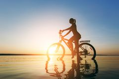 A strong blonde woman in a colorful suit sits on the bicycle in the water at sunset on a warm summer day. Fitness concept. Sky bac. The strong blonde woman in a Stock Photos