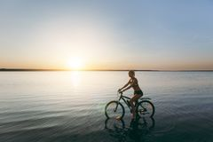 A strong blonde woman in a colorful suit sits on the bicycle in the water at sunset on a warm summer day. Fitness concept. Sky bac. The strong blonde woman in a Stock Photography