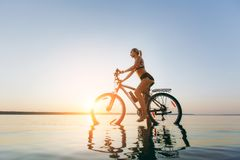A strong blonde woman in a colorful suit sits on the bicycle in the water at sunset on a warm summer day. Fitness concept. Sky bac. The strong blonde woman in a Royalty Free Stock Images