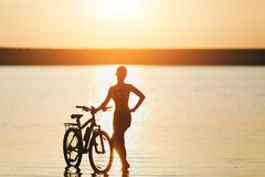 A strong blonde woman in a colorful suit stands near the bicycle in the water at sunset on a warm summer day. Fitness concept. Sky Stock Photo