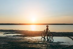 A strong blonde woman in a colorful suit stands near the bicycle in the water at sunset on a warm summer day. Fitness concept. Sky. The strong blonde woman in a Royalty Free Stock Images