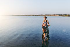 A strong blonde woman in a colorful suit stands near the bicycle in the water at sunset on a warm summer day. Fitness concept. Sky Royalty Free Stock Image