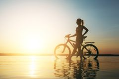 A strong blonde woman in a colorful suit stands near the bicycle in the water at sunset on a warm summer day. Fitness concept. Sky. The strong blonde woman in a Stock Image