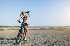 A strong blonde woman in a colorful suit and sunglasses stands near a bicycle, drinks water from a black bottle in a desert area. Royalty Free Stock Image