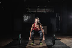 Strong blonde woman exercising with barbell in gym royalty free stock photo