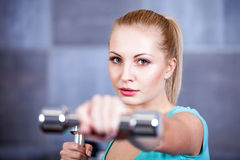 Strong blonde woman weightlifting at the gym, doing shoulders exercise Royalty Free Stock Images