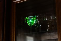 Strong blue laser pointer hits a crystal glass in the wardrobe royalty free stock photo