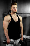 Strong bodybuilder athlete with dumbbells in gym Royalty Free Stock Photos