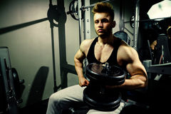 Strong bodybuilder athlete with heavy  dumbbells in gym Stock Photography